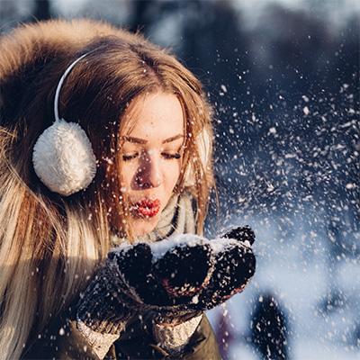 Femme en manteau d'hiver soufflant dans de la neige
